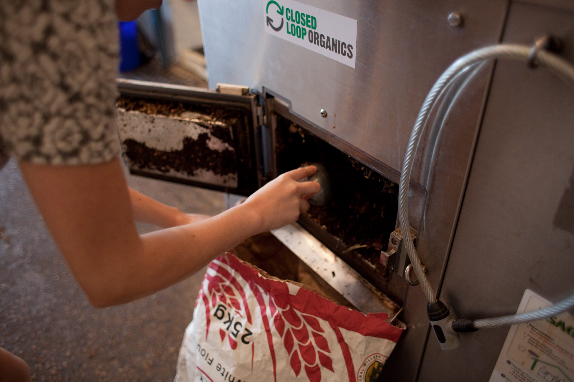 Rebecca Irving bags compost from the composting machine. Once bagged, the compost can be collected for free. Silo has a heated composter; it is an anaerobic digester (no air) and they use an activator to get it going. It is able to convert food waste, paper/wooden cutlery waste to compost in one day. The resulting compost is given away to customers, suppliers and allotment holders.