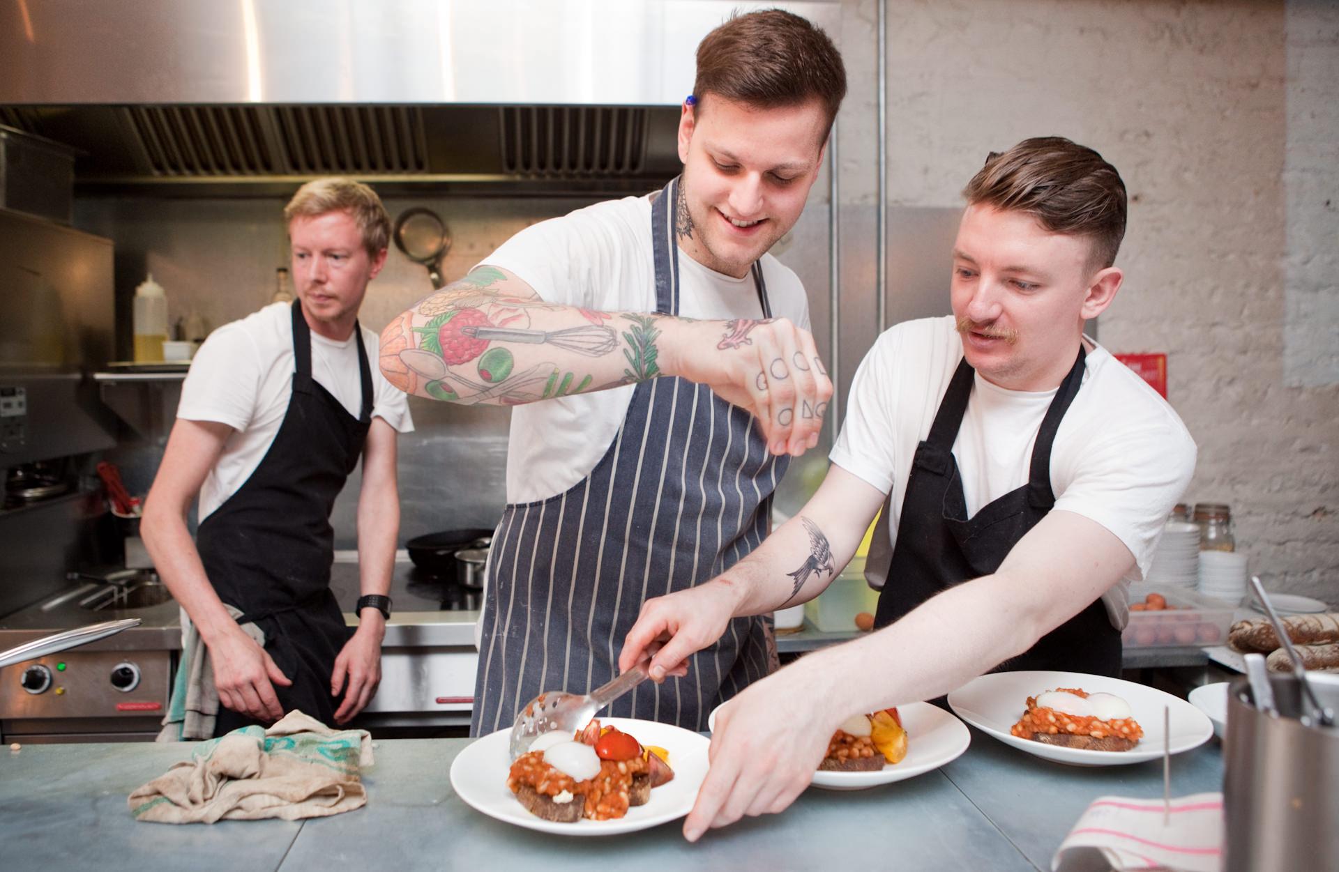 L-R; Head Chef, Kim Sheppard, Blair Hammond and James Mcilveen prepare food in the service kitchen.