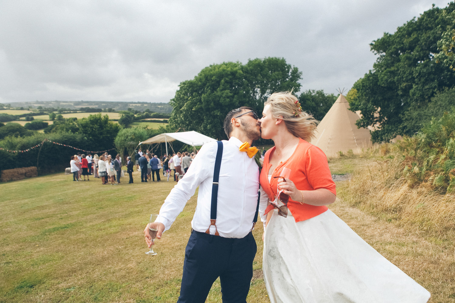 Lara & Atilla's Burnicombe Farm Tipi Wedding. This was a really colourful, outdoor wedding with an eclectic bunch of people - Atilla's Turish family and London hipsters. The wedding ceremony was held outside then people moved into the tipi as the storm clouds gathered.