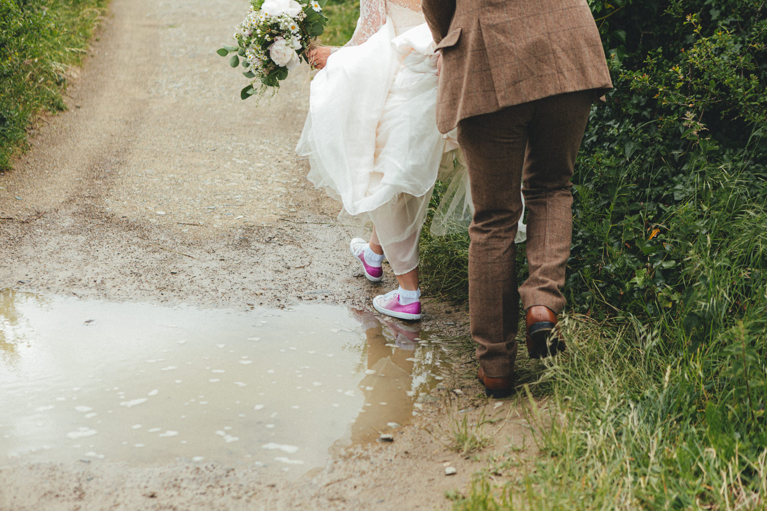Puddle, wet weather, walking. Bride on her way to the church. Bride walking. Pathway. Archway. Cornish Tipi Wedding Photographer. Wedding Photography at Cornish Tipi Weddings on the coast of North Cornwall. Cornish Tipi Wedding is set in a wooded valley, surrounded by ancient woodlands
