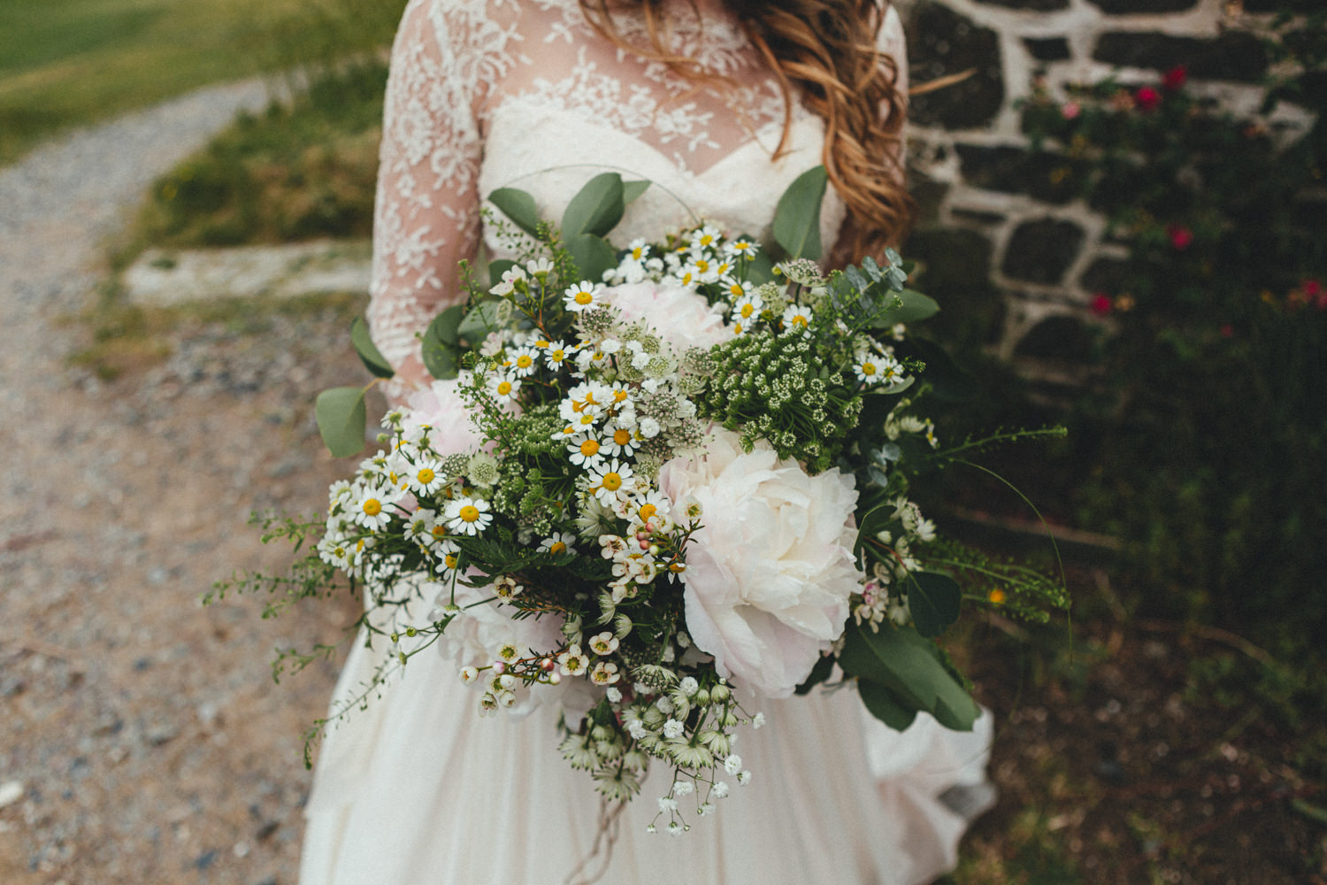 Bridal bouquet. Bouquet with daisies. Bouquet with wildflowers. St Enodoc Church. St Enodoc Church in Cornwall. Cornwall wedding. Wedding in Cornwall
