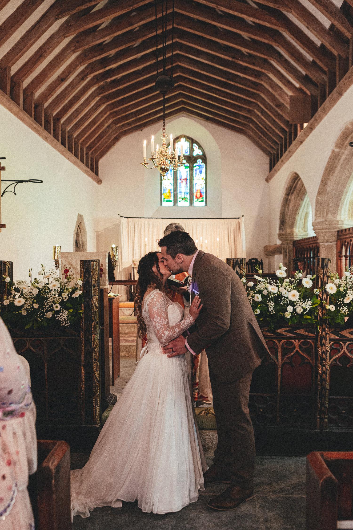 Bride and groom kiss, St Enodoc Church wedding photography