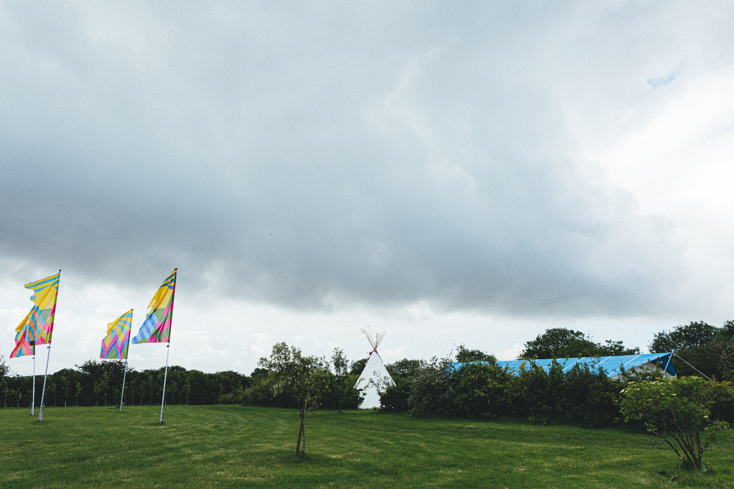 View of tipi and flags. Wedding venue. Cornish Tipi Wedding Photographer. Wedding Photography at Cornish Tipi Weddings on the coast of North Cornwall. Cornish Tipi Wedding is set in a wooded valley, surrounded by ancient woodlands