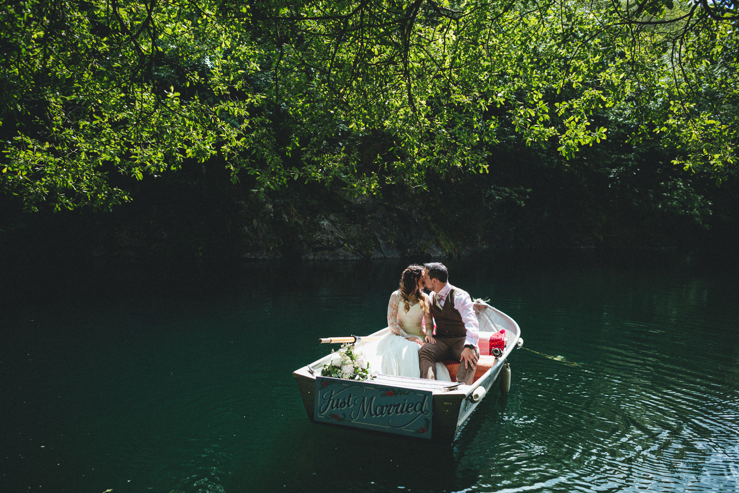 couple in a wedding boat saying just married, Cornish Tipi Wedding Photographer, Cornish Tipi Weddings, Wedding Photography at Cornish Tipi weddings, lakeside portraits