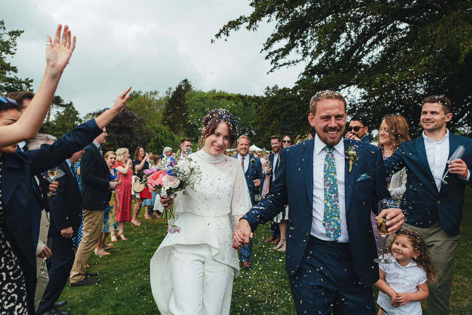 confetti, newlyweds, confetti line, outdoor confetti, documentary photography, wedding guests, green wedding, eco wedding, sharpham gardens wedding photography, outdoor wedding at sharpham house, garden wedding, garden wedding at sharpham house, spring wedding, wedding at sharpham, sharpham house, sharpham gardens, wedding photography, devon wedding, wedding in devon, wedding at sharpham house, devon wedding photographer