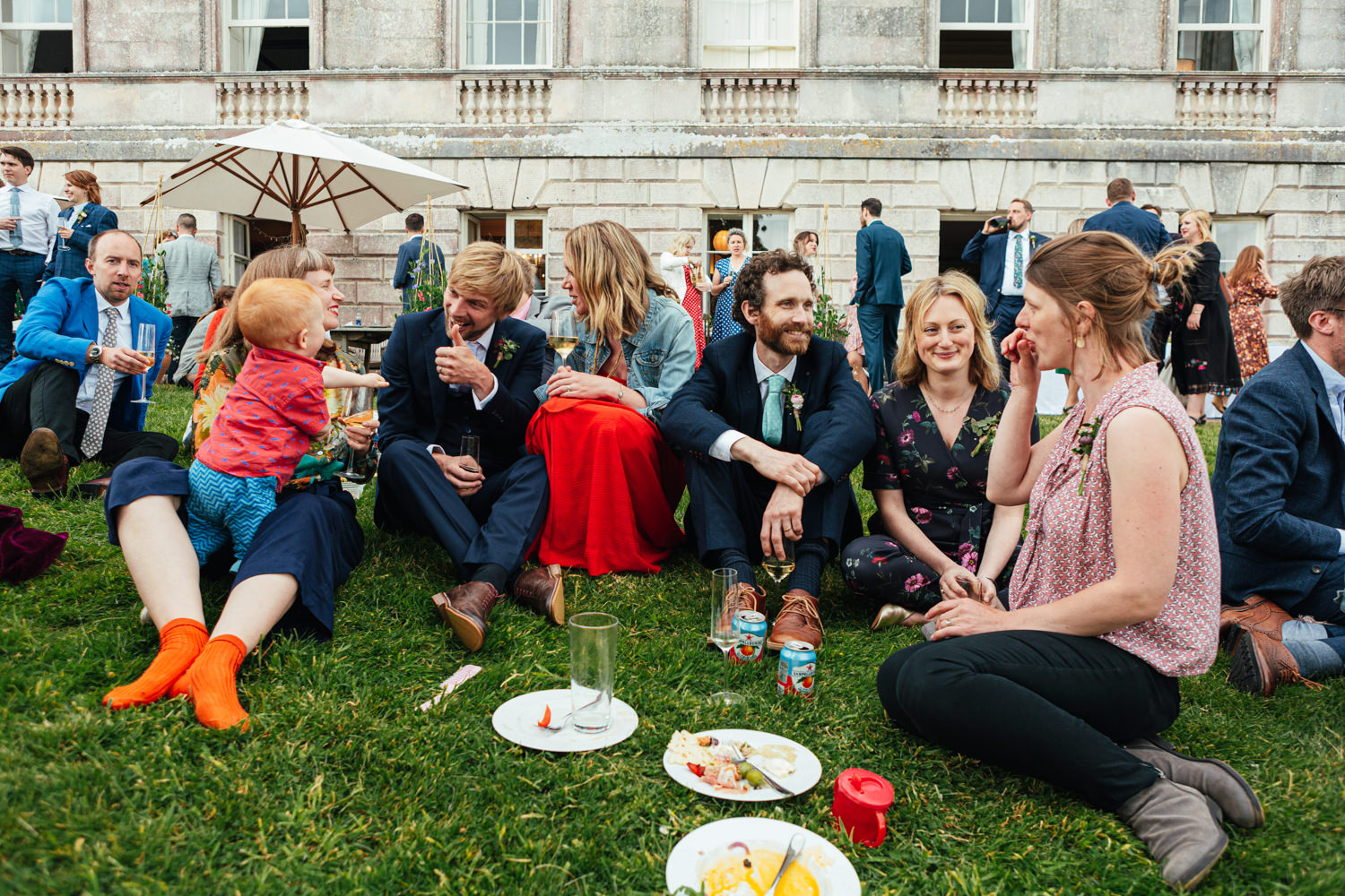 wedding guests, sharpham house, sharpham gardens, sharpham gardens wedding photography, colourful clothing, colour, food, drinks, grass, guests sitting on grass, outdoor wedding reception