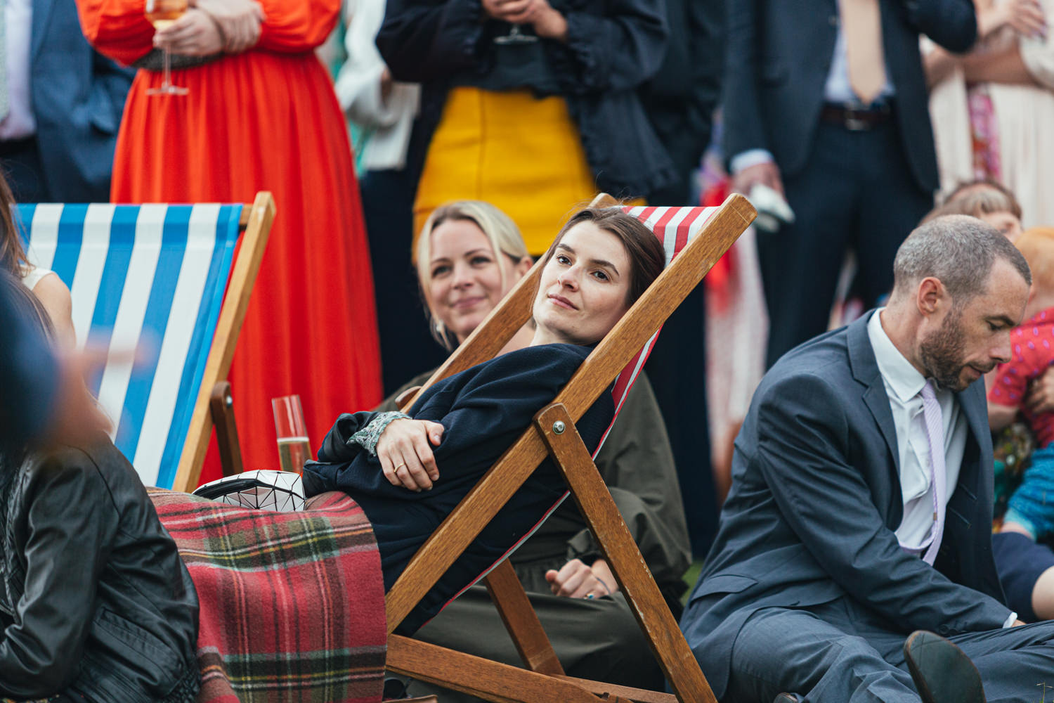 wedding guest sat on a deck chair, wedding speeches, champagne, wedding guests, sharpham house, sharpham gardens, sharpham gardens wedding photography, colourful clothing, deck chair, drinks, outdoor wedding reception
