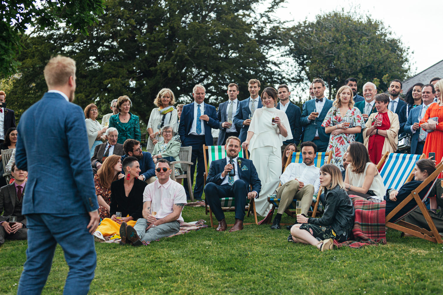 wedding guests sat on a deck chairs, grass, guests sat on grass, wedding speeches, champagne, wedding guests, sharpham house, sharpham gardens, sharpham gardens wedding photography, colourful clothing, deck chair, drinks, outdoor wedding reception