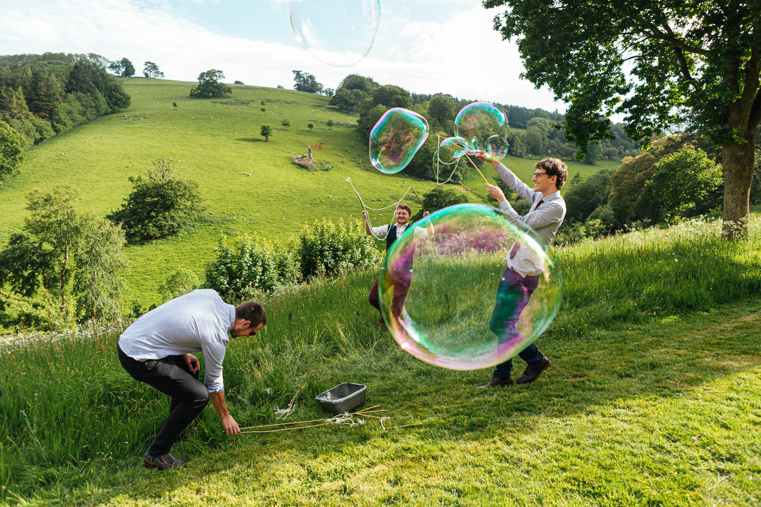 wedding guests blowing bubbles, sharpham gardens wedding photography