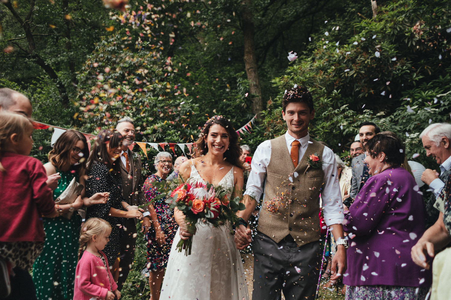 confetti line, bride and groom, guests throwing confetti at couple, colourful wedding, woodland wedding, great wood camp wedding, great wood camp wedding photography, forest wedding