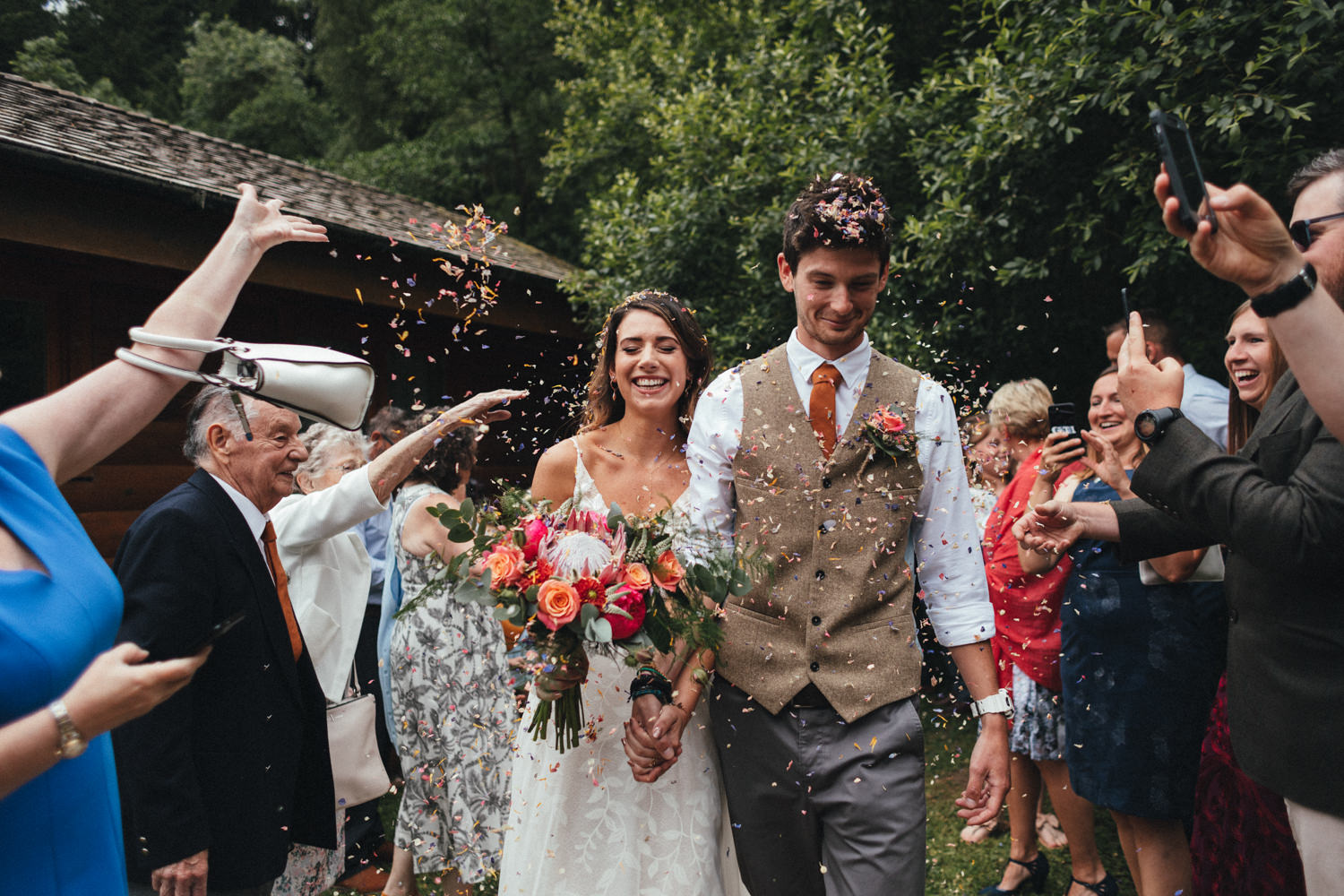 confetti line, bride and groom, guests throwing confetti at couple, colourful wedding, woodland wedding, great wood camp wedding, great wood camp wedding photography, forest wedding, Somerset Wedding