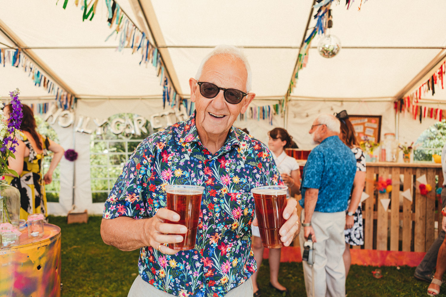 wedding guests with colourful shirt and beer