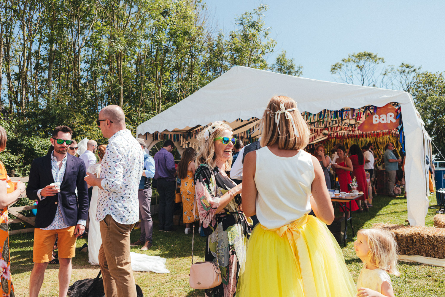 guests chat by the marquee, Holsome Park Wedding Photography, festival wedding, wedding guests, outdoor wedding, summer wedding