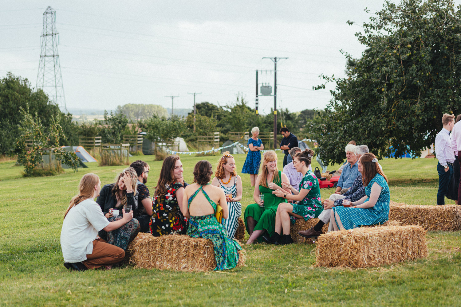 haybales, guests relaxing on haybales at a wedding, outdoor wedding photography, farm wedding, devon wedding, devon wedding photographer, alternative wedding, eco friendly wedding, green wedding